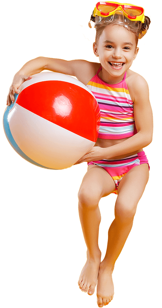 A young girl in a striped bathing suit and diving mask on her head jumps up laughing, holding a beach ball with her arms.