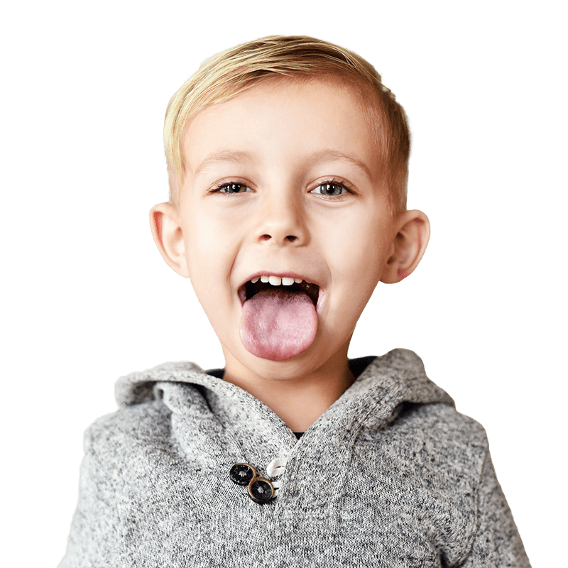 A boy in a gray hoodie holds his tongue out happily smiling with his mouth open.