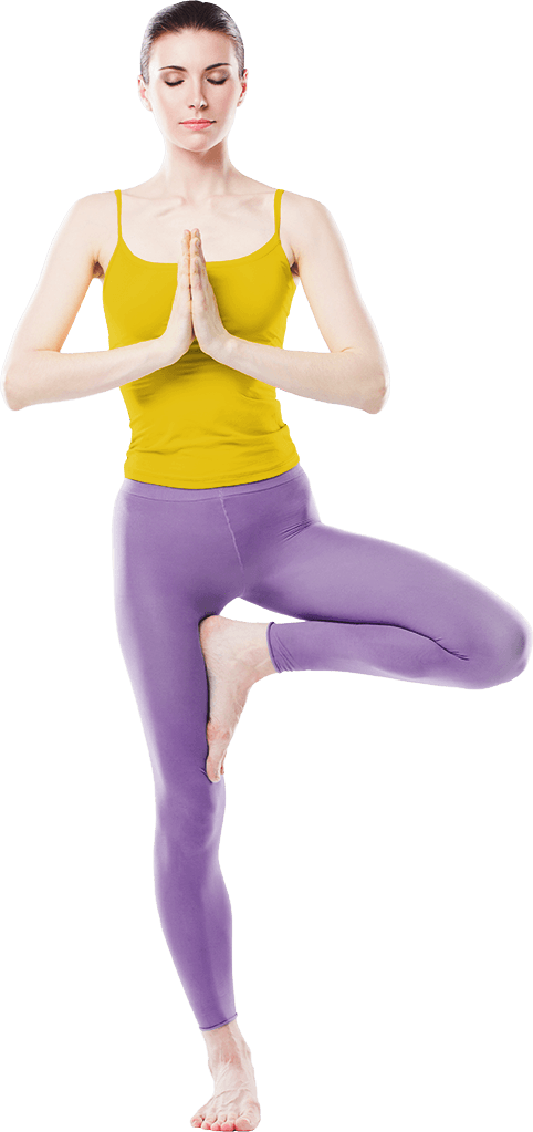 A sporty woman is standing in a yoga figure with her eyes closed on her right leg. Her left leg is angled up to the leg and she holds her palms pressed together in front of her breast.