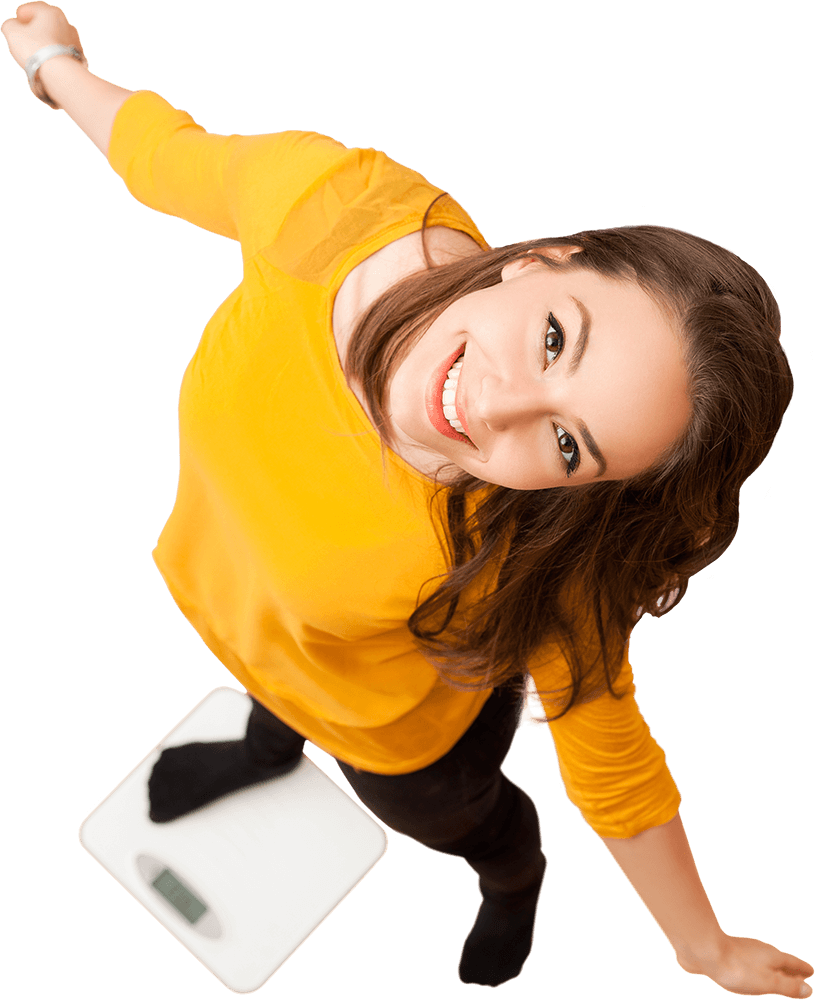 A young woman stands with one leg and outstretched arms on a bathroom scale. She looks up at the camera, smiling.